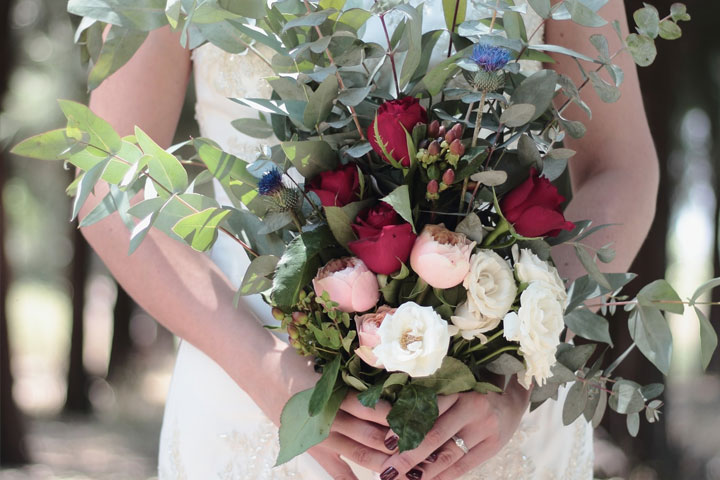 A bride holding a bouquet of fresh red, pink and white flowers.
